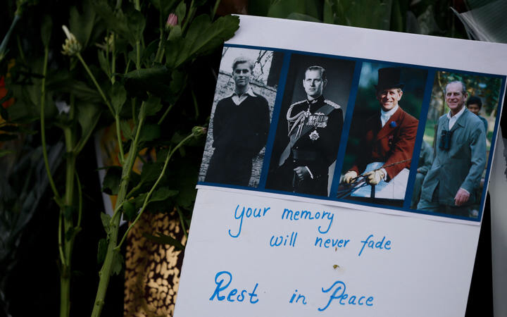 A tribute message for Prince Philip amid flowers outside Buckingham Palace.